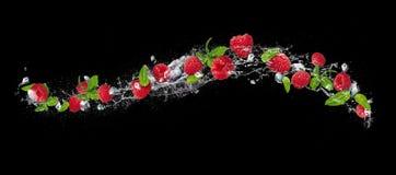 Raspberries falling in water splash on black background. Pieces of raspberries with mint leaves and ice cubes falling in water splash, isolated on black Stock Photo