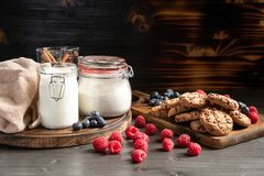 Raspberries in foreground, milk and cookies in backround royalty free stock photography