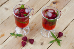 Raspberries fresh drinks with ice and mint on wooden table. Selective focus Royalty Free Stock Images