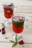 Raspberries fresh drinks with ice and mint on wooden table. Selective focus Stock Photos