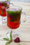 Raspberries fresh drinks with ice and mint on wooden table Stock Image