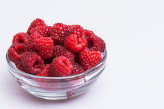 Raspberries. Fresh juicy raspberries in a glass bowl with white background Royalty Free Stock Photography