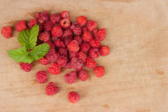 Raspberries. Fresh organic raspberries with leaves on wooden background Stock Images