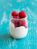 Raspberries and fresh yogurt in a jar. On a turquoise background Stock Image