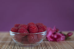 Raspberries in a glass bowl. Horizontal shot of a bowl of raspberries freshly picked and positioned on a bamboo mat, with an out of focus ornamental flower and Royalty Free Stock Images