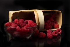 Raspberries in a glass bowl and an inverted basket on a black background.  Royalty Free Stock Image