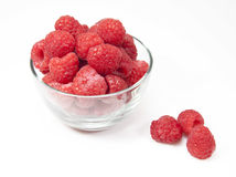 Raspberries in a glass bowl with three loose on the white backgr Royalty Free Stock Photo