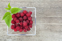 Raspberries in a glass bowl on a wooden background. Royalty Free Stock Photo