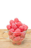 Raspberries in the glass cup on the wood background. Raspberries in the glass cup on the wood desk Stock Photography