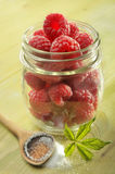 Raspberries in glass jar. Raspberries in a glass jelly jar with a wooden spoon and sugar Stock Images