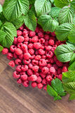 Raspberries and green leaves. Red juicy raspberries and green leaves on wooden table.Copy space Stock Images