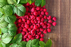 Raspberries and green leaves. Red raspberries and green leaves on wooden table Stock Images
