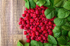 Raspberries and green leaves. Red raspberries and green leaves on wooden table Royalty Free Stock Image