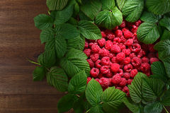 Raspberries and green leaves. Red raspberries and green leaves on wooden table Stock Photo