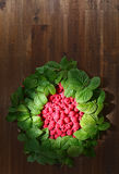 Raspberries and green leaves. Red raspberries and green leaves on wooden table Stock Photos