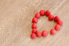 Raspberries heart. The horizontal picture of the raspberries in a shape of heart on wooden background royalty free stock photos