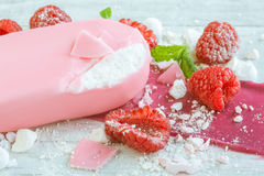 Raspberries with ice cream in pink chocolate. And white petals of rose on wooden background Stock Images