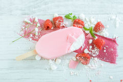 Raspberries with ice cream in pink chocolate. And white petals of rose on wooden background Stock Photos