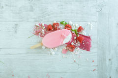 Raspberries with ice cream in pink chocolate. And white petals of rose on wooden background Stock Image