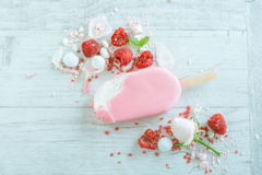 Raspberries with ice cream in pink chocolate. And white petals of rose on wooden background Royalty Free Stock Photography