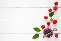 Raspberries jam and fresh berries with copy space on white table. Flat lay, top view Royalty Free Stock Photo