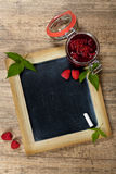 Raspberries jam. Fresh Raspberries jam with chalkboard. Selective focus Royalty Free Stock Photography