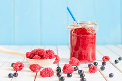 Raspberries jam in mason jar and fresh berries on. Rural wooden table Stock Photos