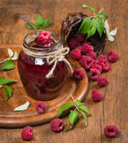Raspberries jam. Raspberry preserve in glass jar and fresh raspberries  in a basket is scattered on a wooden table Royalty Free Stock Photography