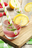 Raspberries and juice. In glass on cutting board on grey wooden background Stock Photo