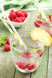 Raspberries and juice. In glass on green wooden background Stock Image