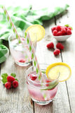 Raspberries and juice. In glass on grey wooden background Royalty Free Stock Photo