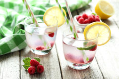 Raspberries and juice. In glass on grey wooden background Stock Photography