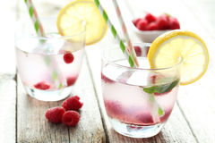 Raspberries and juice. In glass on grey wooden background Royalty Free Stock Image