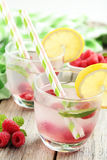 Raspberries and juice. In glass on grey wooden background Royalty Free Stock Images