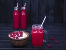Raspberries juice in a glass mug and muesli made from raw raspberry, oat flakes with yogurt and honey on black wooden background,. Red raspberries juice in glass Stock Photos