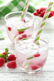 Raspberries and juice. In glass on white wooden background Stock Image