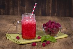 Raspberries juice smoothie shake in glass mug and raw raspberry on wooden background, close up Royalty Free Stock Images