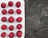 Raspberries laid out in row on white wooden board Stock Image