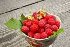 Raspberries with leaves in the Cup. Raspberries in a Cup on wooden surface the view from the top Stock Photography