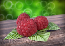 Raspberries with leaves on wooden desk. 3D render Royalty Free Stock Images