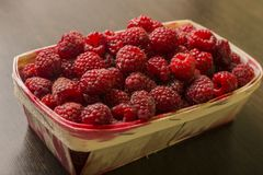 Raspberry in a basket on a wooden background. Raspberries lie in a basket on a wooden background Royalty Free Stock Images