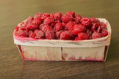 Raspberry in a basket on a wooden background. Raspberries lie in a basket on a wooden background Royalty Free Stock Photo
