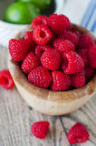 Raspberries and limes. In a wooden board stock image