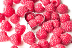 Raspberries in a metal heart on a white background Stock Images