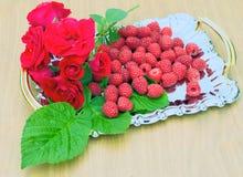 Raspberries are on a metal tray. Raspberries and red roses are on a metal tray Royalty Free Stock Image