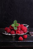 Raspberries. In a metal vase on a black background stock photos