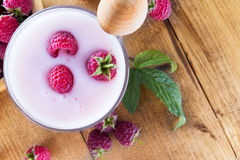 Raspberries with milk shake on the wooden background.  Stock Photos