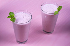 Raspberries milkshake garnished with mint on pink wooden background. Raspberries milkshake garnished with mint on pink wooden background Royalty Free Stock Photography