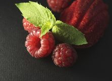 Raspberries, mint leaf and red sponge cake on black background. Closeup Royalty Free Stock Photo