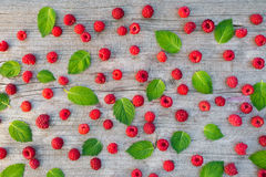 Raspberries and mint leaves. Fresh raspberries and mint leaves patterned over wooden background Royalty Free Stock Images